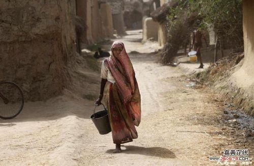 妇女提着水桶去取水