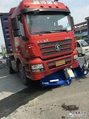 三轮车被卡集装厢大车车头底下